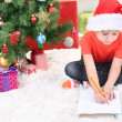 Little boy in Santa hat writes letter to Santa Claus — Stock Photo #18170037