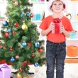 Little boy in Santa hat stands near Christmas tree with gift in his hands — Stock Photo