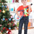 Little boy stands near Christmas tree with badminton rackets — Stock Photo #18170059