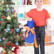 Little boy stands near Christmas tree with flippers — Stock Photo #18170061