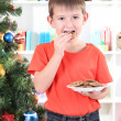 Little boy near Christmas tree eats cookies — Stock Photo