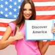 Stock Photo: Young woman young woman holding tablet on background of American flag
