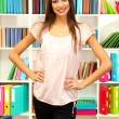 Young attractive female student in library — Stock Photo #18170157