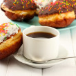 Tasty donuts on color plate on light wooden background - Photo