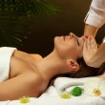 Portrait of beautiful woman taking head massage on green background — Stock Photo #18170397