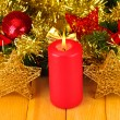 Christmas composition with candles and decorations in red and gold colors on wooden background — Stock Photo