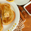 White bread toast with honey and cup of coffee on wooden table - Photo