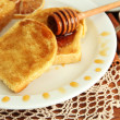 White bread toast with honey on wooden table - Photo