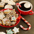 Christmas treats on plate and cup of coffe on wooden table close-up - Photo