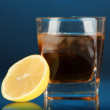 Glass of whiskey with ice and lemon on blue background — Stock Photo