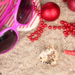 Christmas balls,seashells andh beach accessories on sand, close-up — Stock Photo