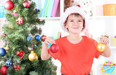 Little boy in Santa hat decorates Christmas tree in room — Zdjęcie stockowe
