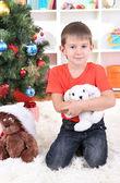 Malý chlapec sedí blízko vánoční stromeček s dárky v rukou — Stockfoto