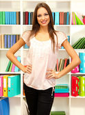 Young attractive female student in library — Stock Photo