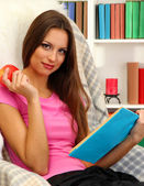 Portrait of female eating apple and reading book at home — Stock Photo