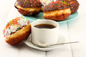Tasty donuts on color plate on light wooden background — Stock Photo