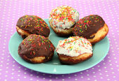 Tasty donuts on color plate on color background — Stock Photo