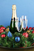 Beautiful Christmas wreath in composition with champagne on blue background — Stock Photo