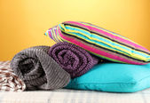 Plaids and color pillows on yellow background — Stock Photo