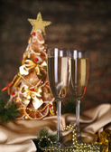 Beautiful christmas tree and glasses of champagne on shine grey background — Stock Photo