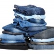 Stock Photo: Many jeans stacked in piles isolated on white