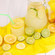 Citrus lemonade in glass and pitcher of citrus around on yellow fabric on white wooden table close-up — Stock Photo