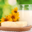 Butter on wooden holder surrounded by flowers and milk on natural background close-up — Stock Photo
