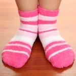 Legs female in striped socks on laminate floor — Stock Photo #18273055