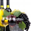 Bottles and glasses of wine and grapes in basket, isolated on white - Stock Photo