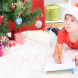 Little boy in Santa hat writes letter to Santa Claus — Stock Photo #18274499