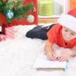 Little boy in Santa hat writes letter to Santa Claus — Stock Photo #18274517