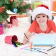 Little boy in Santa hat writes letter to Santa Claus — Stock Photo #18274527