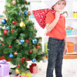 Little boy in Santa hat stands near Christmas tree holding bag with gifts — Stock Photo