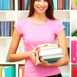 Young attractive female student holding her school books in library — Stock Photo #18274761
