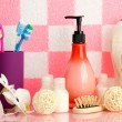 Bath accessories on shelf in bathroom on pink tile wall background — Stock fotografie