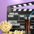 Movie clapperboard, cola and popcorn on purple background — Stock Photo