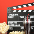 Movie clapperboard, cola and popcorn on red background — Stock Photo