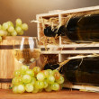 Wooden case with wine bottle, barrel, wineglass and grape on wooden table on brown background — Stock Photo