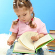 Cute little girl with colorful books, on blue background — Stock Photo #18276225