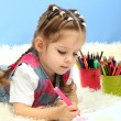 Cute little girl playing with multicolor pencils, on blue background — Stock Photo #18276231