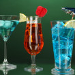 Alcoholic cocktails with ice on darck green background — Stock Photo