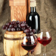 Composition of wine,box and grapes on wooden barrel on sackcloth — Stock Photo