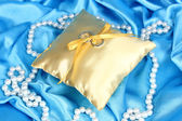 Wedding rings on satin pillow on blue cloth background — Stock Photo