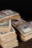 Stacks of dollars on wooden table on black background — Stock Photo