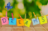 The word Dreams on wooden table on natural background — Stock Photo