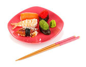 Delicious sushi served on red plate isolated on white — 图库照片