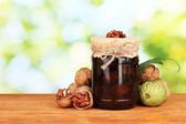 Jam-jar of walnuts on wooden table on green background — Stock Photo