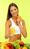 Beautiful young woman with fruits and vegetables and glass of juice, on green background — Stock Photo