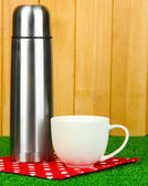 Metal thermos with cup on grass on wooden background — Stock Photo