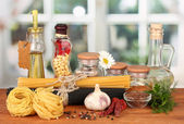 Pasta spaghetti, vegetables and spices on wooden table on bright background — Stock Photo